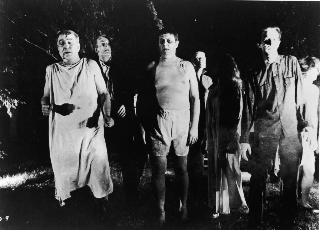 A line of undead 'zombies' walk through a field in the night in a still from the film, 'Night Of The Living Dead,' directed by George Romero, 1968. (Photo by Pictorial Parade/Getty Images)